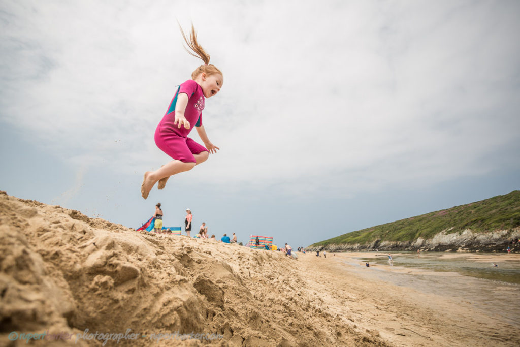 Crantock Beach sand jumping girl daughter